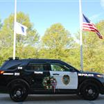Hingham Police vehicle and Veterans Memorial, flag